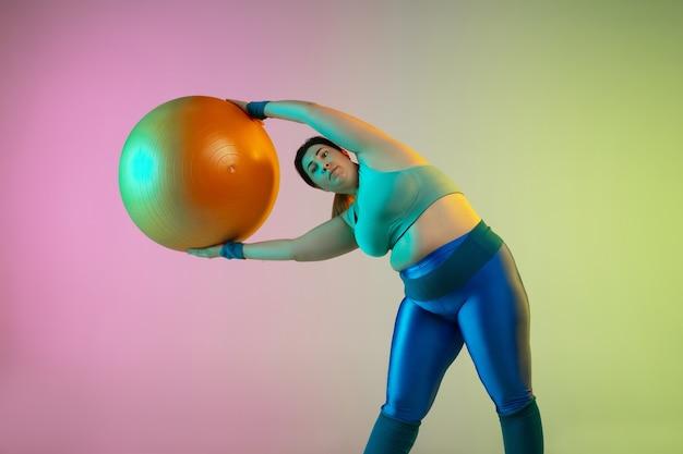Jonge kaukasische plus size vrouwelijke model training op gradiënt paarse groene muur in neonlicht.