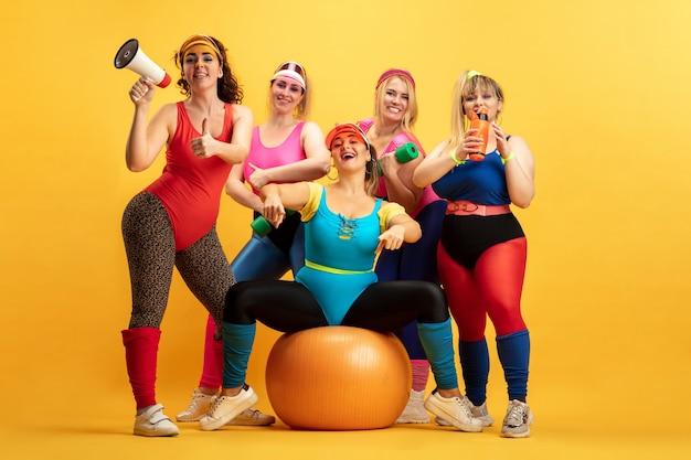 Jonge kaukasische plus size vrouwelijke modellen trainen op gele muur. kopieerruimte. concept van sport, gezonde levensstijl, lichaamspositief, mode. vriendschap, girlpower. stijlvolle vrouw poseren, glimlachend.