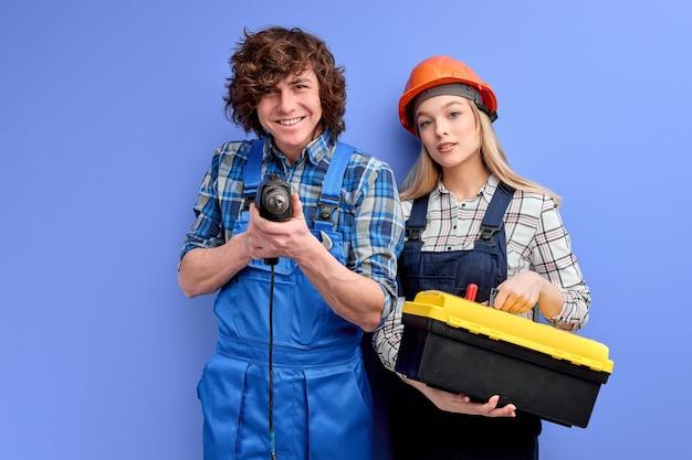 Jonge kaukasische positieve constructeurs met instrumentenhulpmiddelen stellen geïsoleerd op blauwe muur