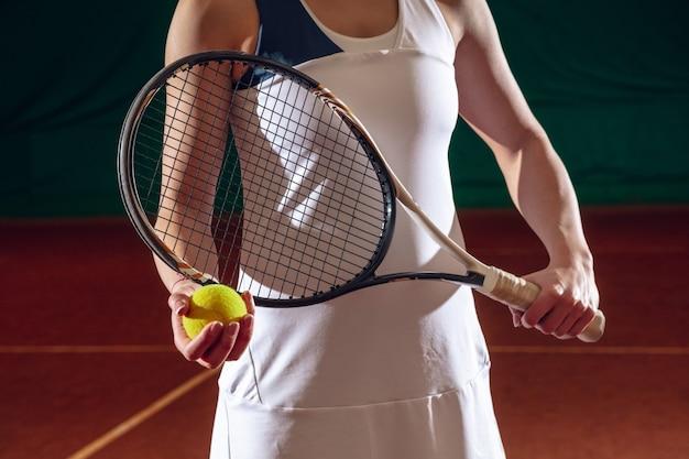 Jonge kaukasische professionele sportvrouw die tennis speelt op de muur van het sporthof. trainen, oefenen in beweging, actie. kracht en energie. beweging, advertentie, sport, gezond levensstijlconcept. detailopname.