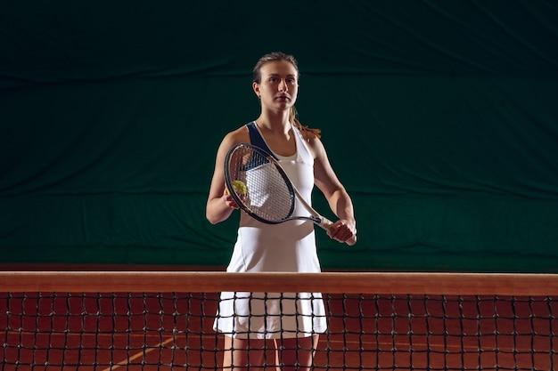 Jonge kaukasische professionele sportvrouw die tennis speelt op de muur van het sporthof. trainen, oefenen in beweging, actie. kracht en energie. beweging, advertentie, sport, gezond levensstijlconcept. vooraanzicht.
