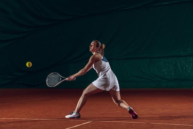Jonge kaukasische professionele sportvrouw die tennis speelt op de muur van het sporthof.