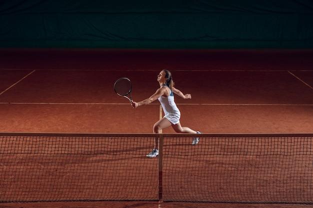 Jonge kaukasische professionele sportvrouw tennissen op sportveld. trainen, oefenen in beweging, actie. kracht en energie. beweging, advertentie, sport, gezond levensstijlconcept. hoge hoek.