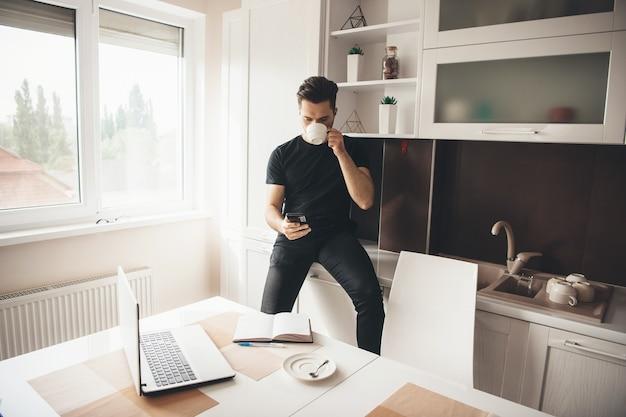 Jonge kaukasische programmeur heeft een pauze, drinkt een kopje koffie en praat via de telefoon in de keuken