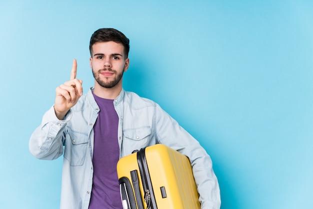 Jonge kaukasische reizigersmens die een koffer geïsoleerd houden tonend nummer één met vinger.