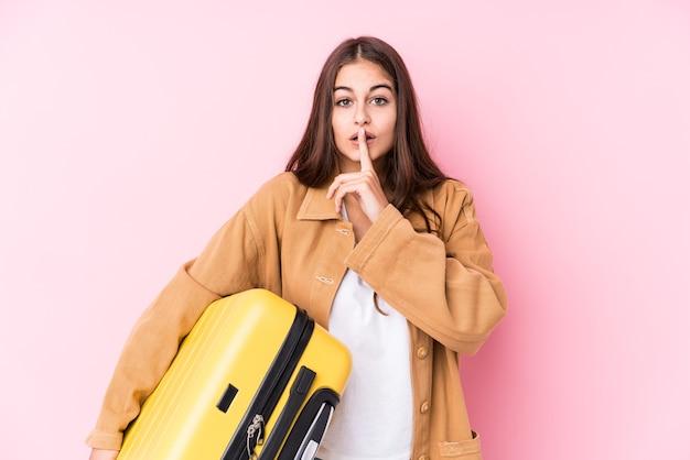 Jonge kaukasische reizigersvrouw die een geïsoleerde koffer houdt die een geheim houdt of om stilte vraagt.