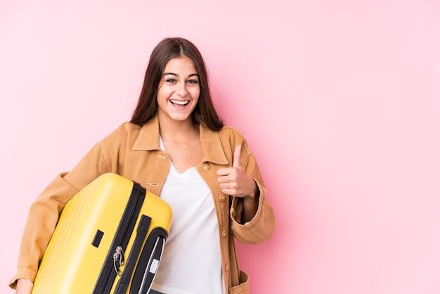 Jonge kaukasische reizigersvrouw die een geïsoleerde koffer houdt en duim opheft