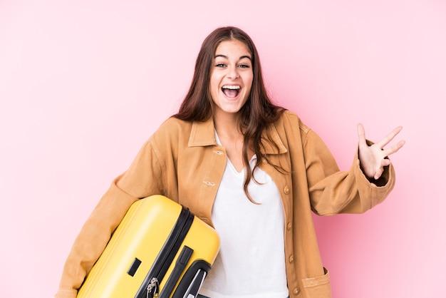 Jonge kaukasische reizigersvrouw die een koffer houdt die een aangename verrassing ontvangt, opgewekt en handen opheft.