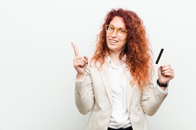 Jonge kaukasische roodharige vrouw die een creditcard houdt die vrolijk met weg wijst met wijsvinger glimlacht.