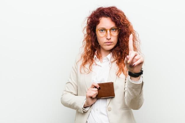 Jonge kaukasische roodharigevrouw die een portefeuille houden die nummer één met vinger tonen.