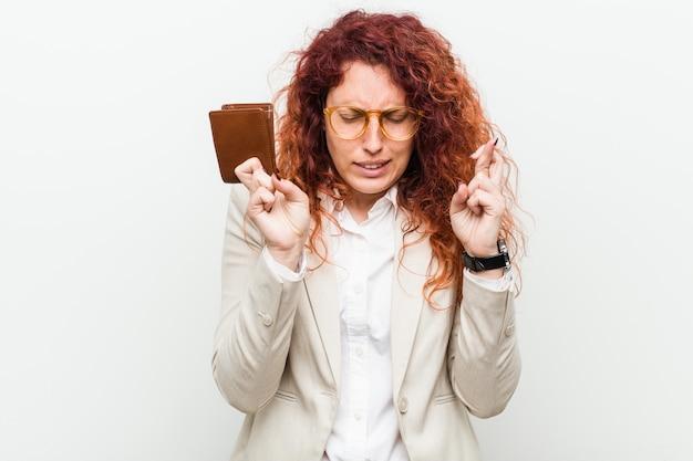 Jonge kaukasische roodharigevrouw die een portefeuille houden die vingers kruisen voor het hebben van geluk