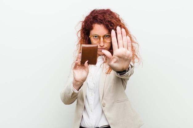 Jonge kaukasische roodharigevrouw die een portefeuille houden die zich met uitgestrekte hand bevinden die eindeteken tonen, die u verhinderen.