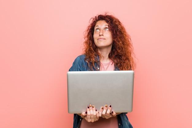 Jonge kaukasische roodharigevrouw die laptop glimlachen houden zeker met gekruiste wapens.