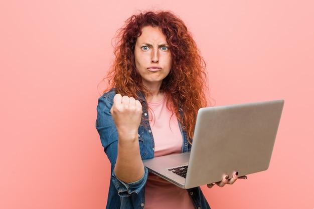 Jonge kaukasische roodharigevrouw die laptop houden die vuist tonen aan camera, agressieve gelaatsuitdrukking.