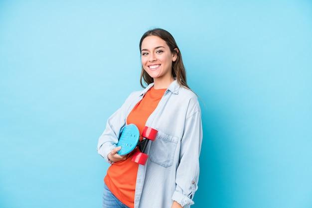 Jonge kaukasische schaatservrouw die op blauwe achtergrond wordt geïsoleerd