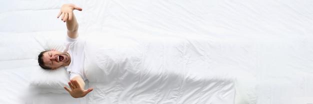 Jonge kaukasische schoonheidsvrouwenslaap op wit bed