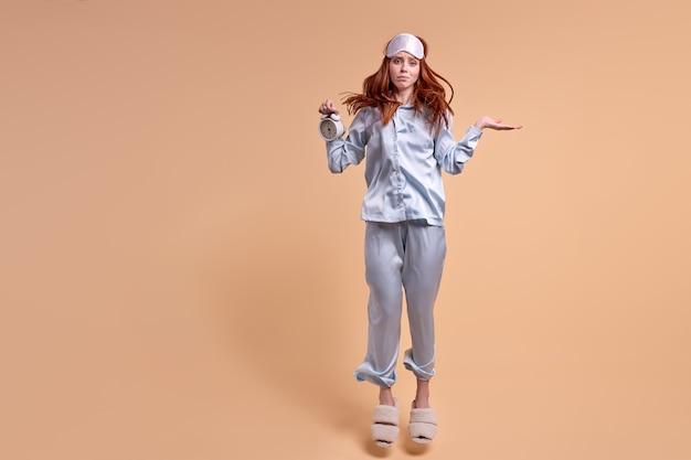Jonge kaukasische slaperige vrouw over geïsoleerde beige achtergrond in pyjama die klok met verstoorde dis...