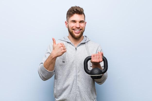 Jonge kaukasische sportman die een halter houdt die en duim opheft