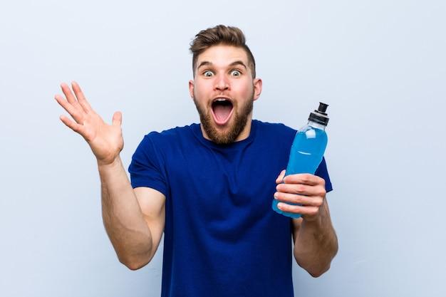 Jonge kaukasische sportman die een isotone drank houdt die een overwinning of een succes viert