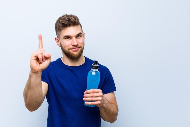Jonge kaukasische sportman die een isotone drank houdt die nummer één met vinger toont.