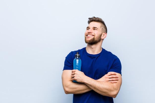 Jonge kaukasische sportman die het isotone drank glimlachen houden zeker met gekruiste wapens.