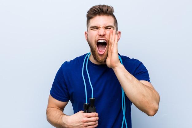 Jonge kaukasische sportman met springtouw schreeuwen opgewekt aan voorzijde.