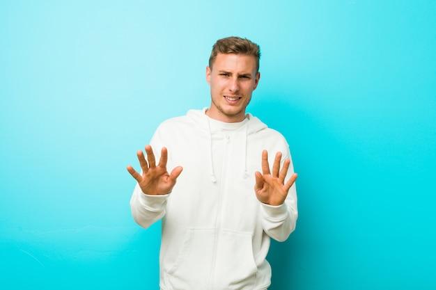 Jonge kaukasische sportmens die iemand verwerpen die een gebaar van afschuw tonen.
