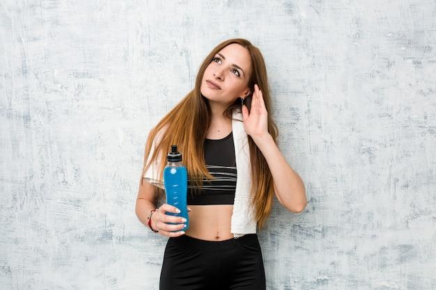 Jonge kaukasische sportvrouw die een isotone drank houdt die aan het luisteren van een roddel probeert.