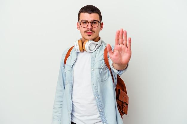 Jonge kaukasische studentenmens die aan muziek luistert die op witte muur wordt geïsoleerd die zich met uitgestrekte hand bevindt die stopbord toont, dat u verhindert.