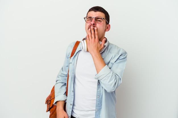 Jonge kaukasische studentenmens die aan muziek op witte geeuw luistert die een moe gebaar toont dat mond met hand behandelt.