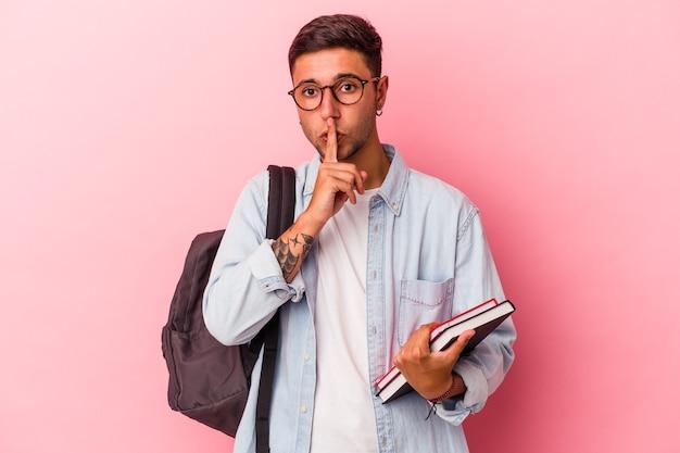 Jonge kaukasische studentenmens die boeken houdt die op roze achtergrond worden geïsoleerd die een geheim houden of om stilte vragen.