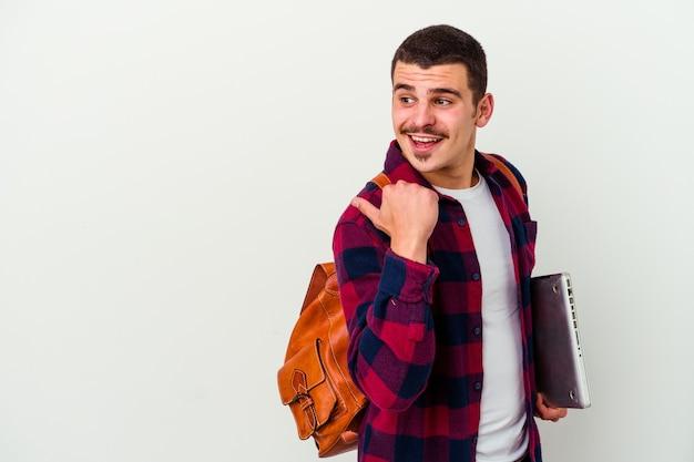 Jonge kaukasische studentenmens die laptop houdt die op witte achtergrond wordt geïsoleerd richt met duimvinger weg, lachend en zorgeloos.