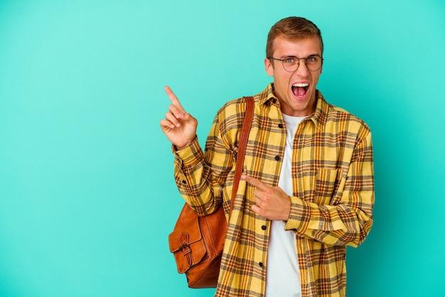 Jonge kaukasische studentenmens die op blauwe muur wordt geïsoleerd die met wijsvingers naar een exemplaarruimte richt, opwinding en verlangen uitdrukt.