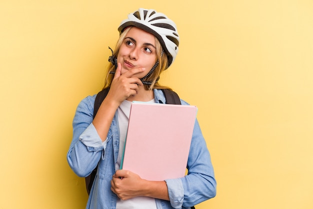 Jonge kaukasische studentenvrouw die een fietshelm draagt die op gele achtergrond wordt geïsoleerd die zijdelings met twijfelachtige en sceptische uitdrukking kijkt.