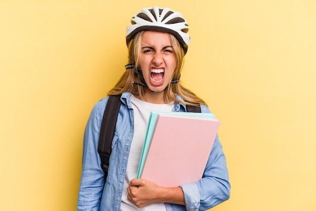 Jonge kaukasische studentenvrouw die een fietshelm draagt die op gele achtergrond wordt geïsoleerd en erg boos en agressief schreeuwt.