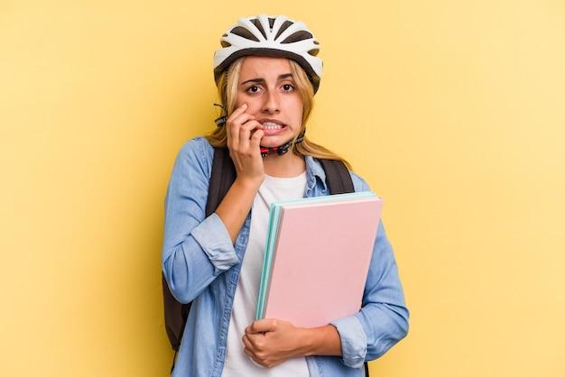 Jonge kaukasische studentenvrouw die een fietshelm draagt die op gele achtergrond wordt geïsoleerd en vingernagels bijt, nerveus en erg angstig.