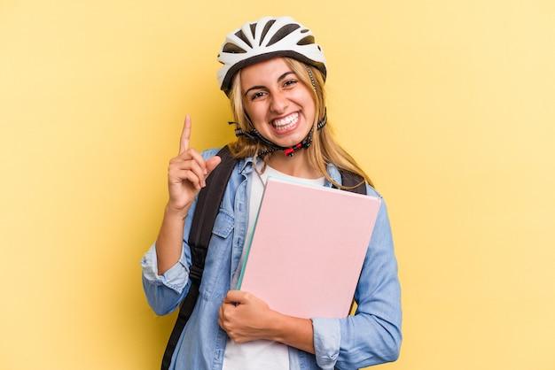 Jonge kaukasische studentenvrouw die een fietshelm draagt die op gele achtergrond wordt geïsoleerd glimlacht en wijst opzij, die iets bij lege ruimte toont.