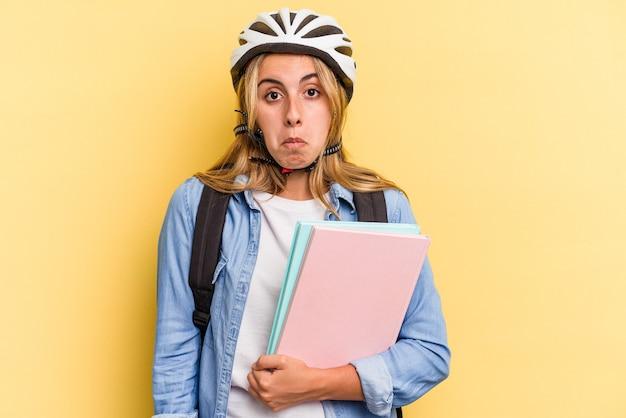 Jonge kaukasische studentenvrouw die een fietshelm draagt die op gele achtergrond wordt geïsoleerd haalt schouders op en verwarde ogen.