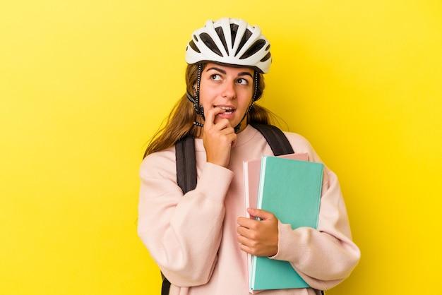 Jonge kaukasische studentenvrouw die een fietshelm draagt die op gele achtergrond wordt geïsoleerd ontspannen denkend over iets dat een exemplaarruimte bekijkt.
