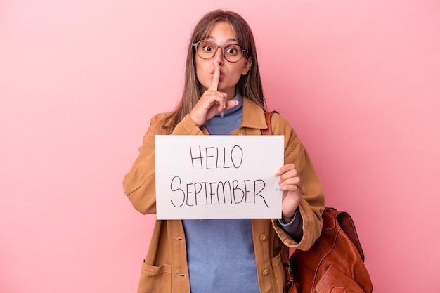 Jonge kaukasische studentenvrouw die hallo september plakkaat houdt dat op roze achtergrond wordt geïsoleerd die een geheim houdt of om stilte vraagt.