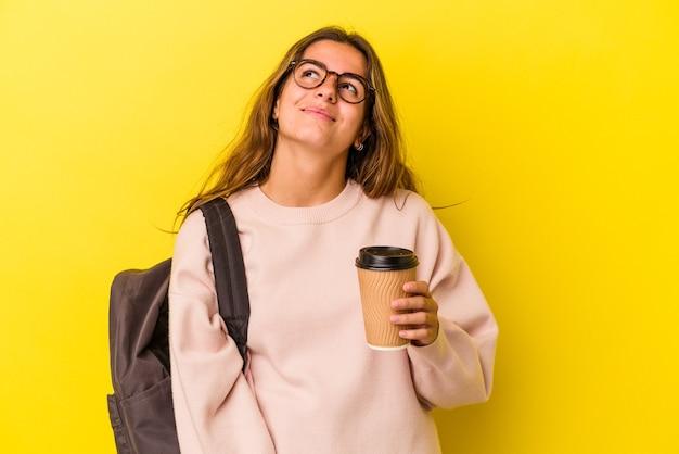 Jonge kaukasische studentenvrouw die koffie houdt die op gele achtergrond wordt geïsoleerd en droomt van het bereiken van doelen en doeleinden