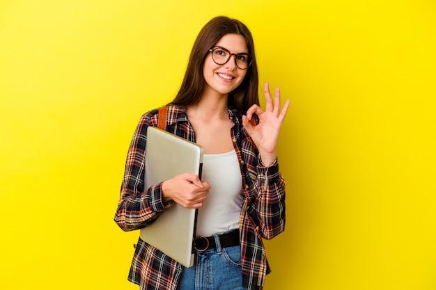 Jonge kaukasische studentenvrouw die laptop houden die op roze muur vrolijk en zelfverzekerd wordt geïsoleerd tonend ok gebaar.