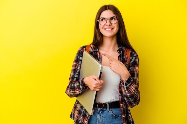 Jonge kaukasische studentenvrouw die laptop houdt die op roze muur wordt geïsoleerd die en opzij glimlacht richt, die iets op lege ruimte toont.