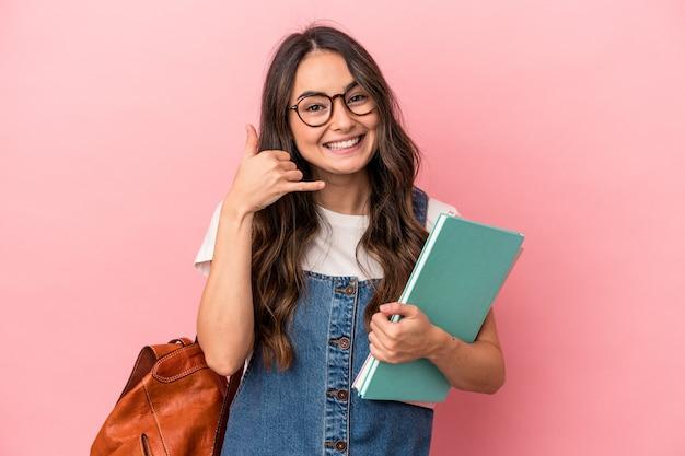 Jonge kaukasische studentenvrouw die op roze achtergrond wordt geïsoleerd die een mobiel telefoongesprekgebaar met vingers toont.