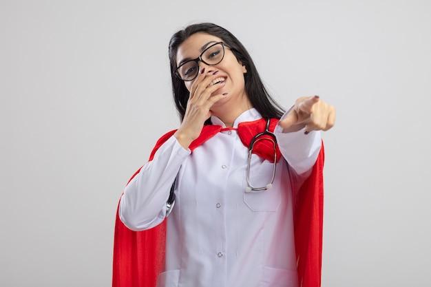 Jonge kaukasische superheld meisje bril en stethoscoop lachen houden hand op mond kijken en wijzend op camera geïsoleerd op een witte achtergrond met kopie ruimte