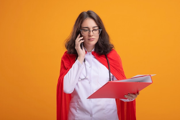Jonge kaukasische superheld meisje in rode cape dragen dokter uniform en stethoscoop met bril met map naar beneden kijken praten over telefoon geïsoleerd op oranje muur met kopie ruimte