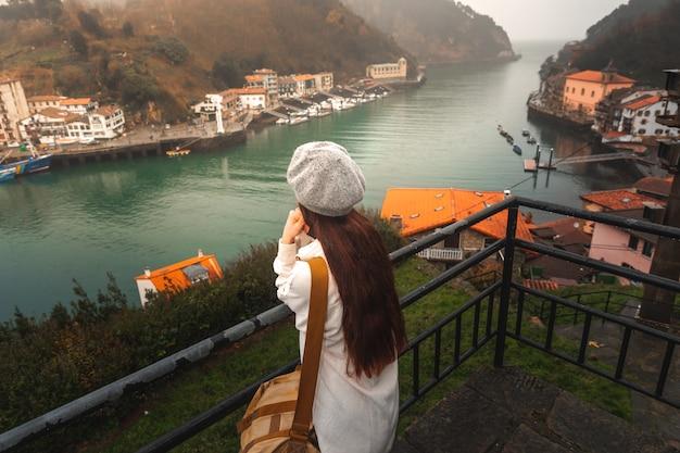 Jonge kaukasische toeristenvrouw die de baai vanuit een hoog gezichtspunt bekijken in pasaia, baskenland.