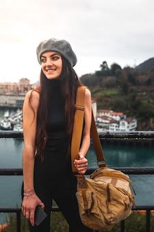 Jonge kaukasische toeristenvrouw die de baai vanuit een hoog gezichtspunt in pasaia bekijkt; baskenland.