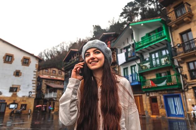 Jonge kaukasische toeristenvrouw die de smartphone in een oude stad met behulp van.