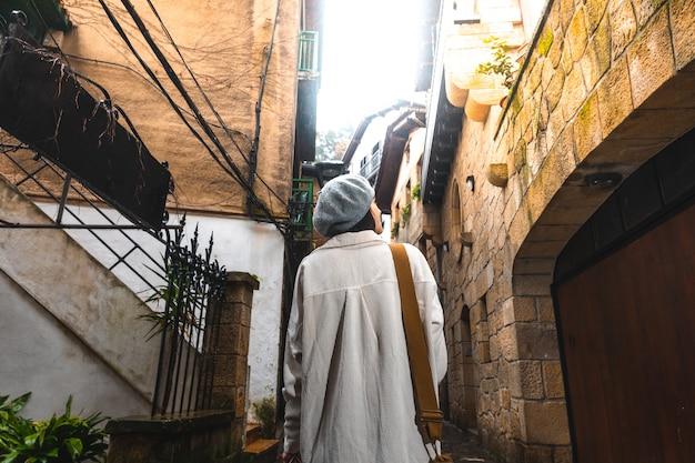 Jonge kaukasische toeristenvrouw die smalle straatjes van een oude stad bezoekt.